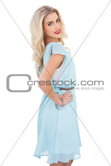 Pretty blonde model in blue dress posing hand on the hip