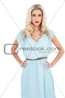 Contemplative blonde model in blue dress posing hands on the hips