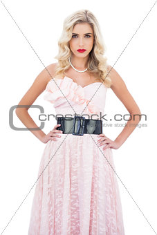 Stern blonde model in pink dress posing hands on the hips and looking at camera