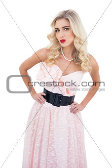 Seductive blonde model in pink dress posing hands on the hips