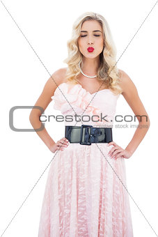 Wondering blonde model in pink dress closing her eyes and posing hands on the hips