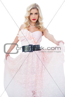 Attractive blonde model in pink dress posing holding her dress