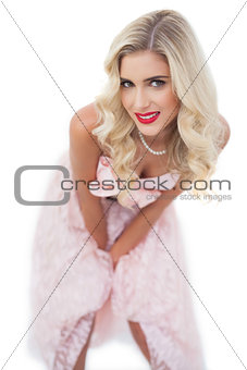 Smiling blonde model in pink dress posing hands on the thighs