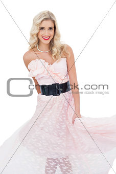 Pleased blonde model in pink dress posing shaking her dress