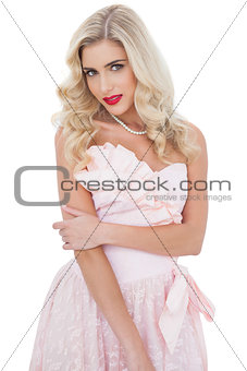 Thoughtful blonde model in pink dress posing holding her arm
