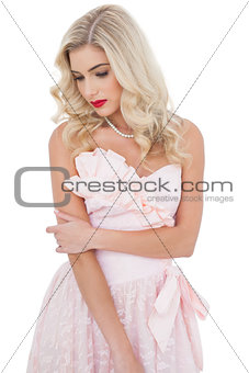 Pensive blonde model in pink dress posing holding her arm