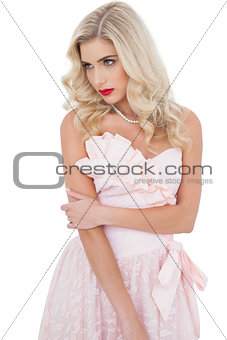 Concentrated blonde model in pink dress posing holding her arm