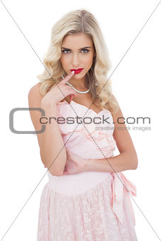Amused blonde model in pink dress posing a finger on the mouth