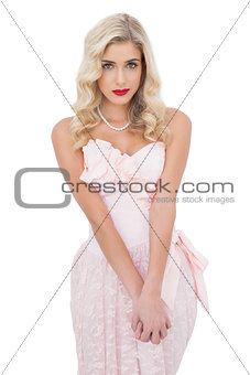 Unsmiling blonde model in pink dress posing looking at camera and holding her hands