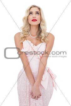 Wondering blonde model in pink dress posing holding her hands and looking up