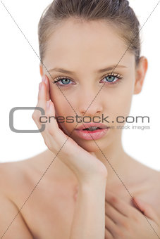 Serious brunette model posing holding her head