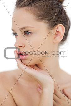 Unsmiling brunette model posing holding her head