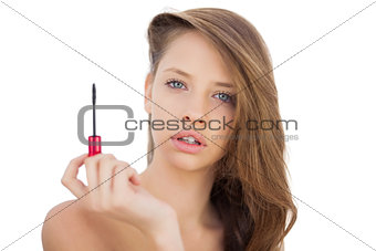 Serious brunette model holding a mascara tube