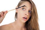 Puzzled brunette model brushing her eyebrows
