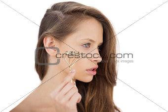 Unsmiling brunette model holding an eyelash curler