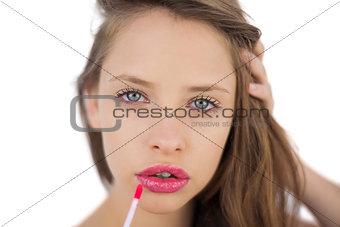 Calm brunette model applying pink gloss on her lips