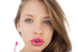 Concentrated brunette model applying pink gloss