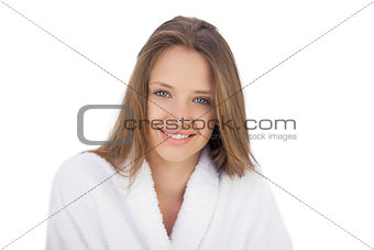 Smiling brunette in bathrobe looking at camera