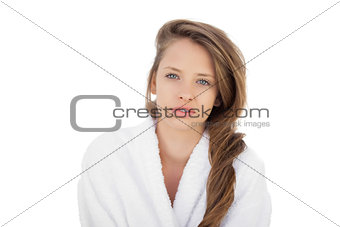 Attractive brunette in bathrobe looking at camera