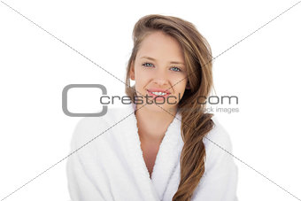 Delighted brunette in bathrobe looking at camera