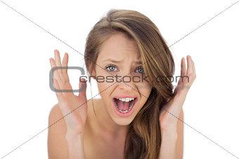 Annoyed brunette model raising her hands and screaming