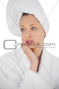 Serious brunette model in bathrobe looking away