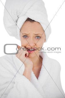 Worried brunette in bathrobe looking at camera