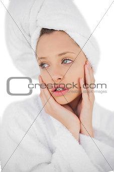 Anxious brunette in bathrobe looking away