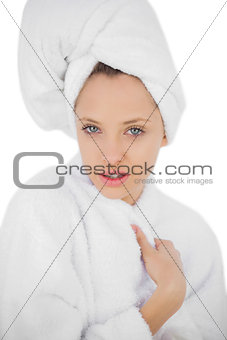 Pleased brunette in bathrobe looking at camera