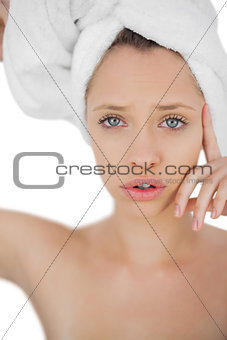 Unsmiling brunette drying her hair looking at camera