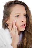 Thoughtful brunette in bathrobe rubbing her cheek with cream