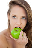 Unsmiling brunette model eating an apple