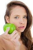 Unsmiling brunette model holding an apple