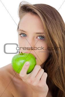Serious brunette model eating an apple