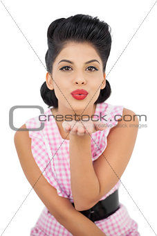 Pleased black hair model blowing a kiss to the camera