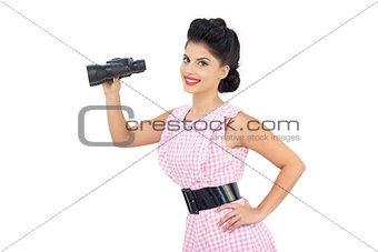 Smiling black hair model holding binoculars