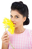 Seductive black hair model smelling a flower