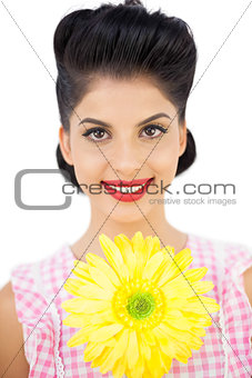 Smiling black hair woman showing a flower
