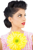 Thoughtful black hair model holding a flower and looking away
