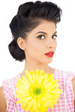Thoughtful black hair model holding a flower and looking at camera