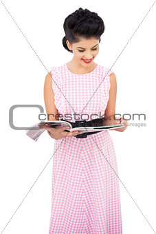 Pleased black hair model reading a magazine