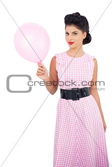 Pleased black hair model holding a pink balloon