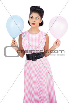 Thoughtful black hair model holding balloons