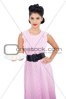 Attractive black hair model presenting a plate of candies