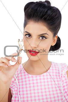 Attractive black hair model holding an eyelash curler