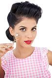 Gorgeous black hair model holding an eyelash curler