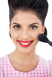 Smiling black hair model applying powder on her cheek