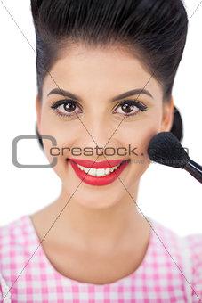 Smiling black hair model applying powder on her cheek