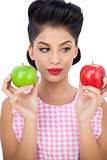 Pensive black hair model holding apples