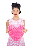 Serious black hair model holding a pink heart shaped pillow